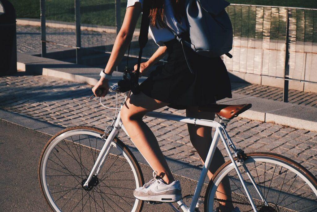 Dziewczyna w spódnicy na białym rowerze